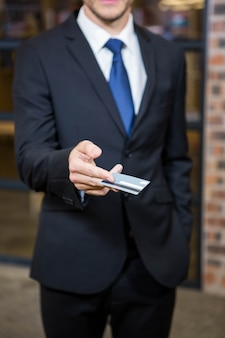 Businessman showing a credit card in office