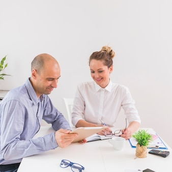 Businessman showing on digital tablet to businesswoman in the office
