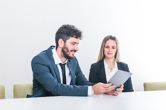 Businessman showing digital tablet to her colleague