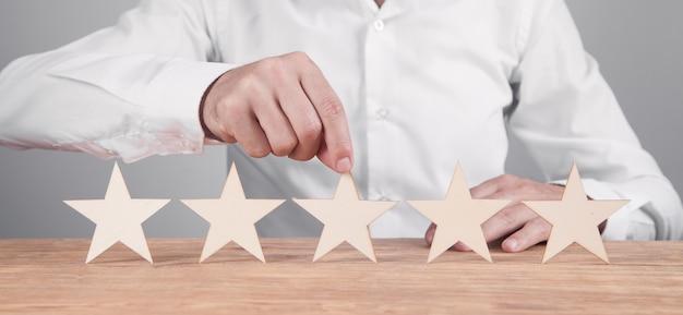Бизнесмен, показывающий пятизвездочный рейтинг