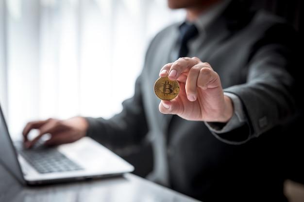 ラップトップを使用しながらビットコインのシンボルと金貨を示すビジネスマン