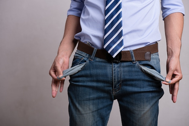Businessman showing his empty pockets. financial difficulties, no money concept.