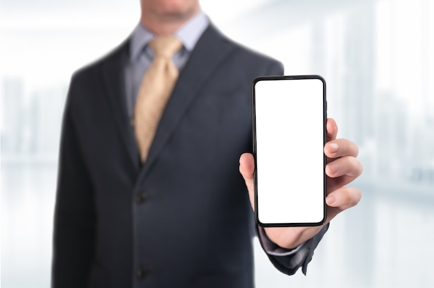 Businessman showing phone. businessman shows cell phone with blank screen. man hand hold smart mobile cell phone with blank white screen. blurred office background