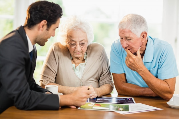 Businessman showing sheets to senior couple at home