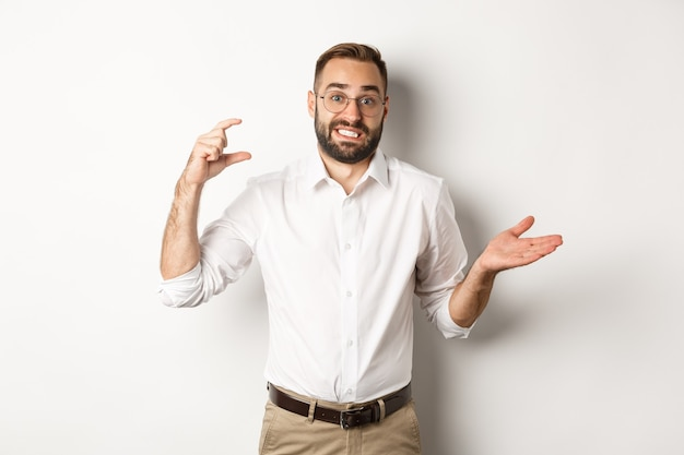 Businessman showing small gesture, looking displeased, shrugging confused, standing against white background.