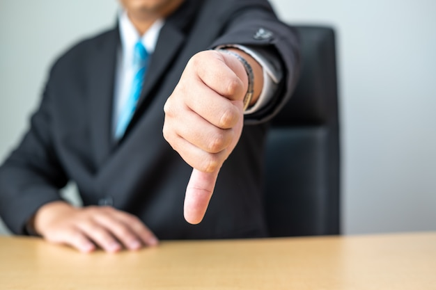 Businessman showing thumbs down on desk