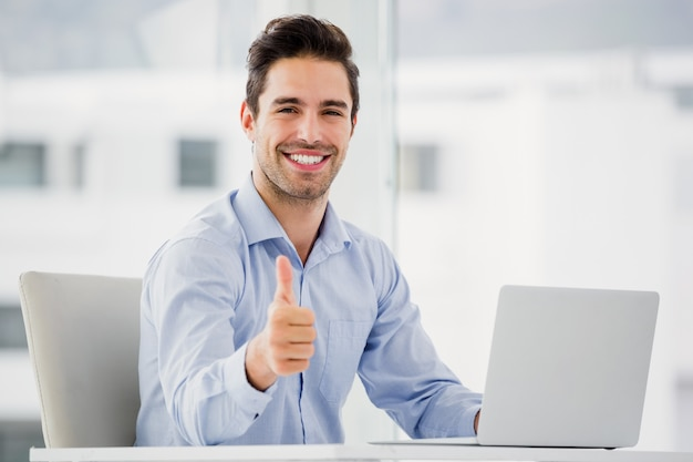 Businessman showing thumbs up while using laptop