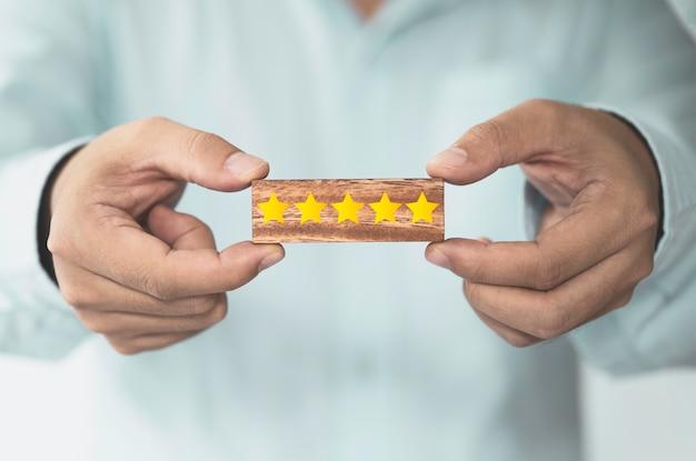 나무 블록 큐브 적 고객 평가에 화면을 인쇄하는 노란색 별 다섯 개를 보여주는 사업가