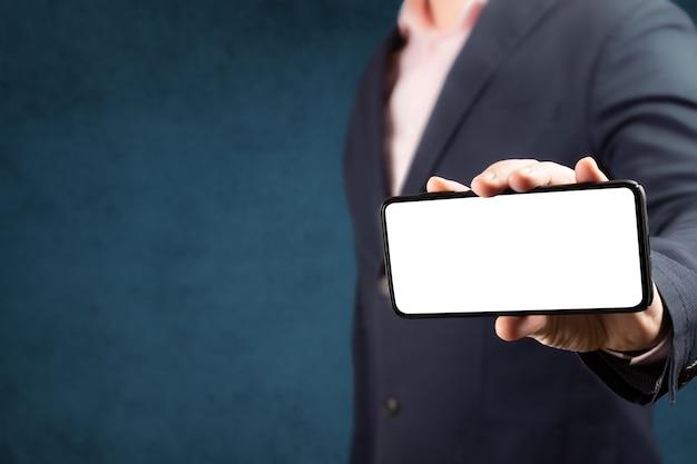 ビジネスマンは、垂直位置で空白の画面で携帯電話を表示します。携帯電話のモックアップ