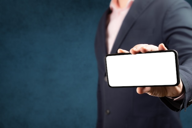 Businessman shows cell phone with blank screen in vertical position. mock up cell mobile smart phone