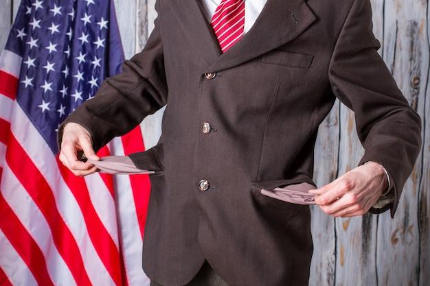 사업가는 빈 주머니를 보여줍니다. 남자의 뒤에 미국 국기입니다. 위기는 갑자기 찾아왔다. 주지사는 부채가 너무 많습니다.