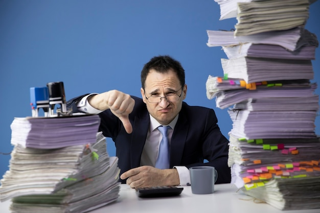 Businessman shows finger down sitting at office desk with huge stack of documents looking sad and depressed