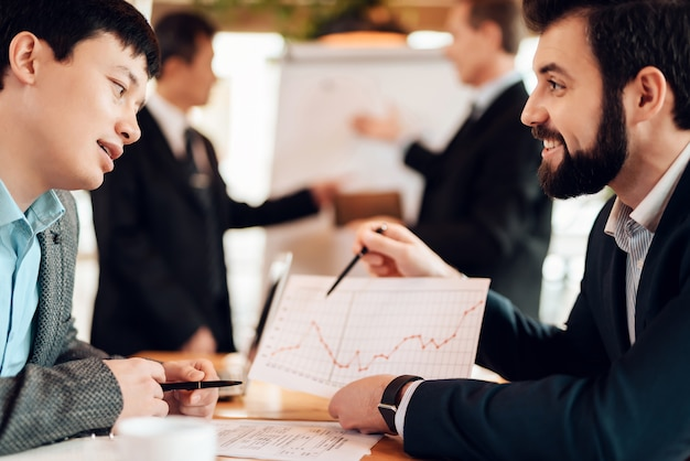 Businessman shows on a schedule to his partner