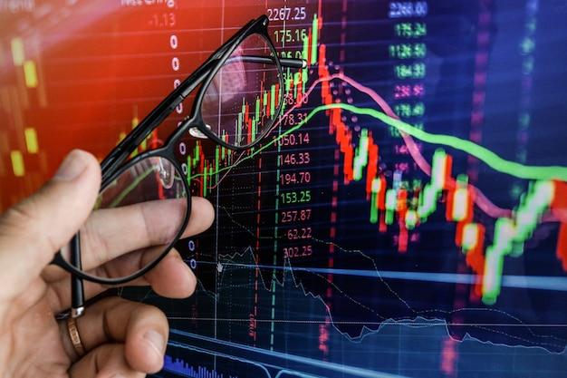 ビジネスマンは成長のグラフをラップトップの画面に表示します