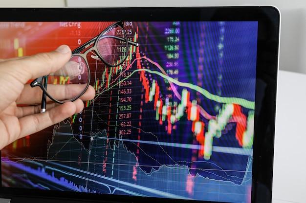Бизнесмен показывает экран на ноутбуке график роста
