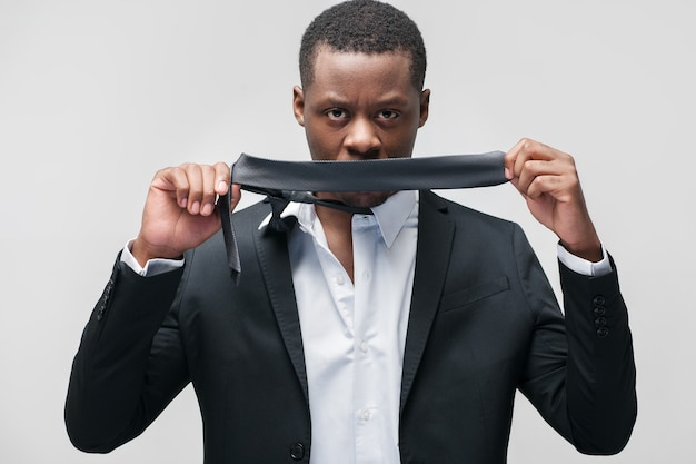 Businessman shutting his mouth with tie