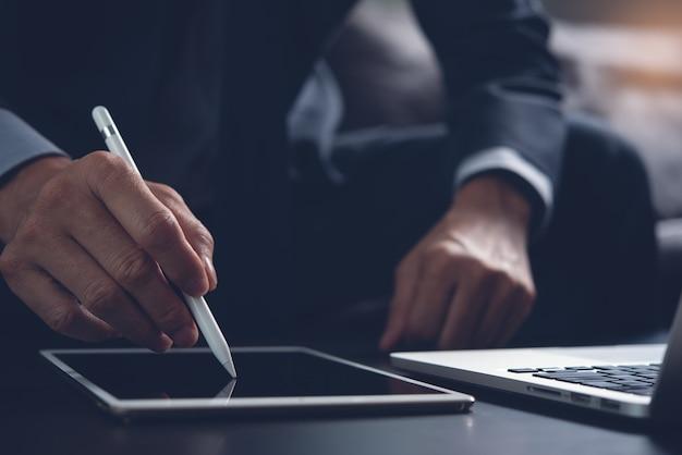Бизнесмен, подписывающий деловой контракт на цифровом планшете в офисе
