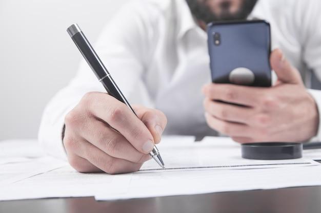 Бизнесмен, подписывающий контракт и использующий смартфон в офисе.