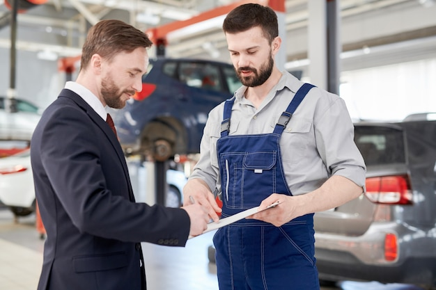 Businessman signing contract in car service