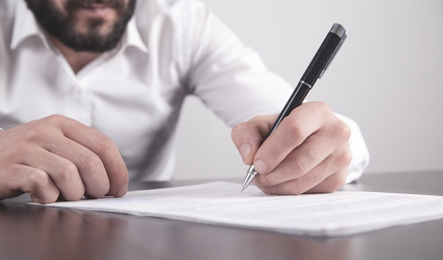 Businessman signing contract in office.