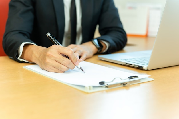 Businessman signing contract paper with pen and laptop in office desk.