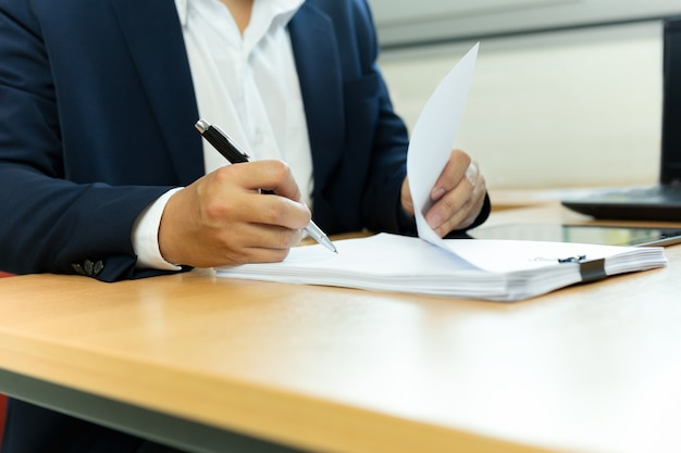 Businessman signing contract paper with pen in office desk.