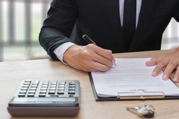 木製の机の上でキーと電卓と契約書に署名しているビジネスマン