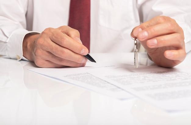 Бизнесмен, подписывающий контракт с ключами в руке. концепция договора недвижимости