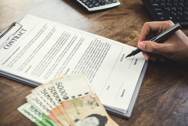 韓国人との契約に署名する実業家は机の上のお金を獲得しました