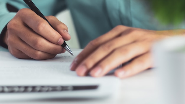 Businessman signing a document after reading the agreement in office