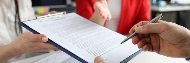 ビジネスマンは、パートナーの概念と取引を行うボールペンのクローズアップで文書に署名