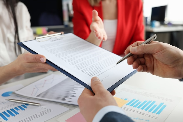 Businessman signing document with ballpoint pen closeup