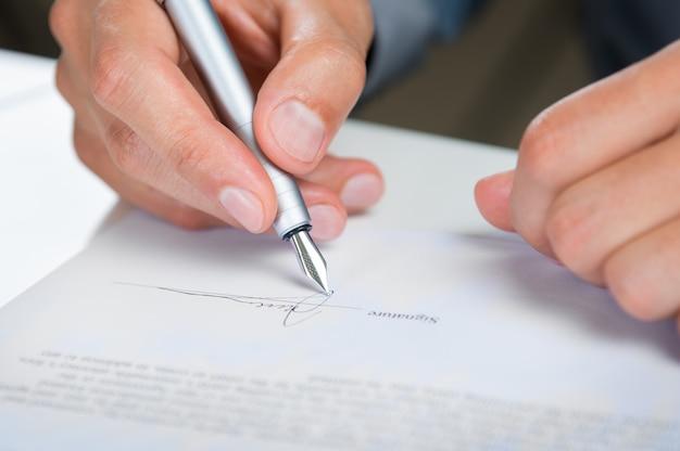Бизнесмен, подписывающий документ