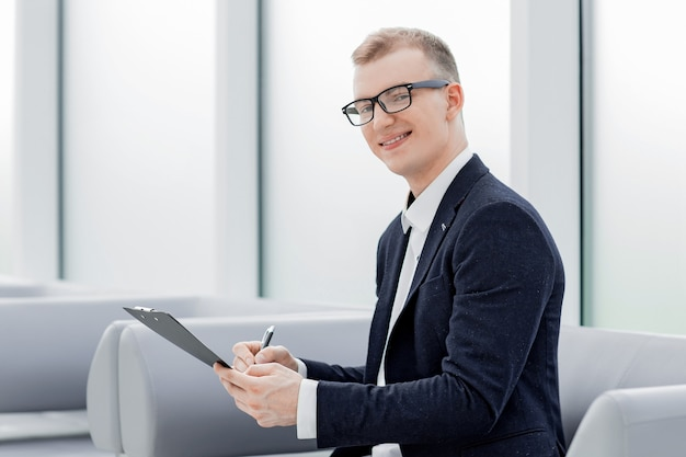 Businessman signs a business document sitting in the office lobby