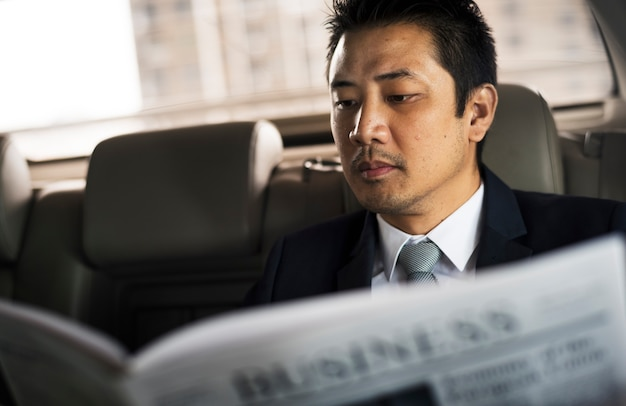 Businessman sit read newspaper inside car