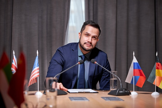 Businessman sit speaking into the microphone at meeting, offering new ideas and solutions for business development. in modern boardroom office. man in suit