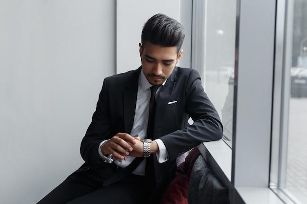 ビジネスマンは窓の周りに座って彼の時計を見ています