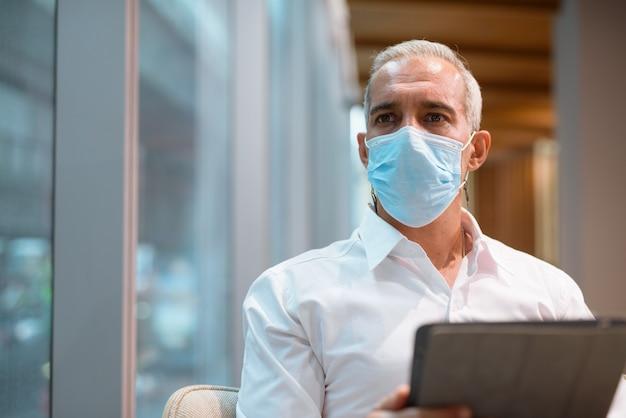 커피숍에 앉아 디지털 태블릿을 사용하는 사업가는 얼굴 마스크와 사회적 거리를 둔 수평 샷을 착용합니다.