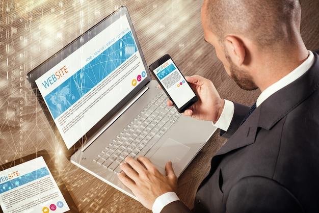 Бизнесмен, сидящий за столом, работающий с планшетом ноутбука и мобильным телефоном