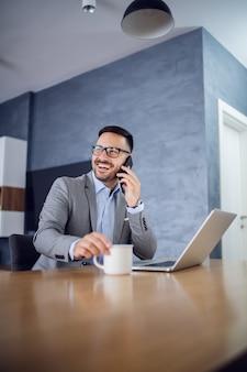 家で座っていると電話をかけるビジネスマン。 Premium写真