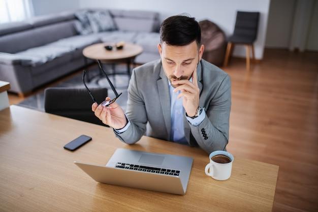 Бизнесмен, сидя у себя дома и с помощью ноутбука.