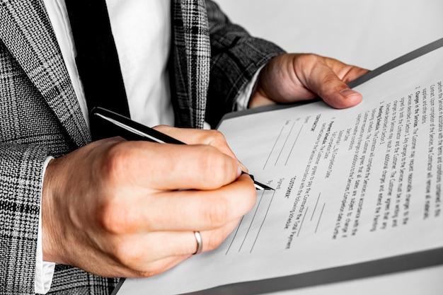 Бизнесмен сидит за офисным столом, подписывая контракт с мелким акцентом на подписи