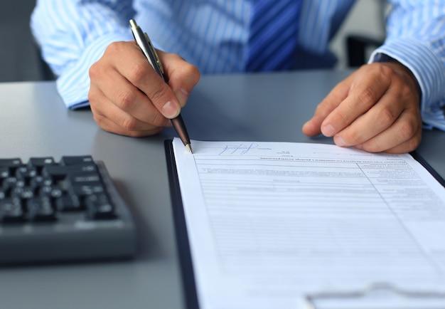 Бизнесмен, сидя за офисным столом, подписывая контракт с неглубоким акцентом на подписи.