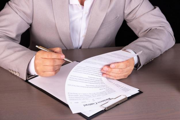 オフィスの机に座っているビジネスマンが契約書に署名