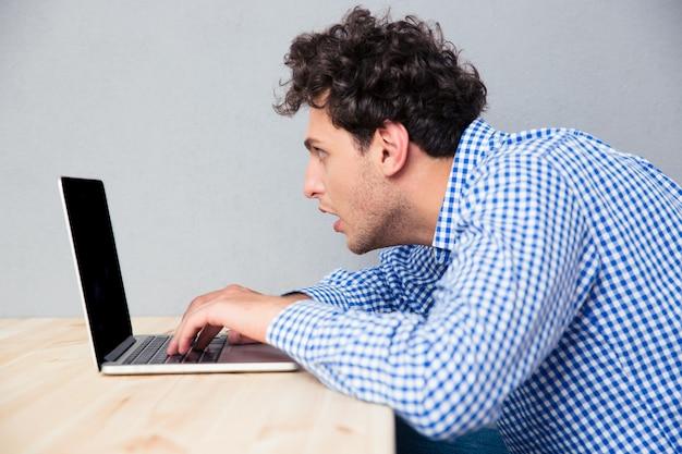 Бизнесмен, сидя за столом и используя ноутбук