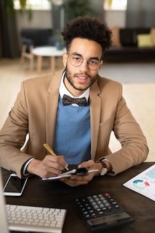Бизнесмен, сидящий за столом, работающий с документами и компьютером и работающий над финансовым проектом в офисе