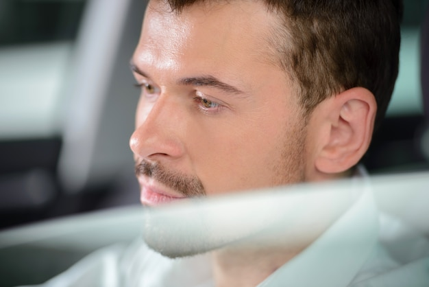 Businessman sitting in car and smiling at camera.