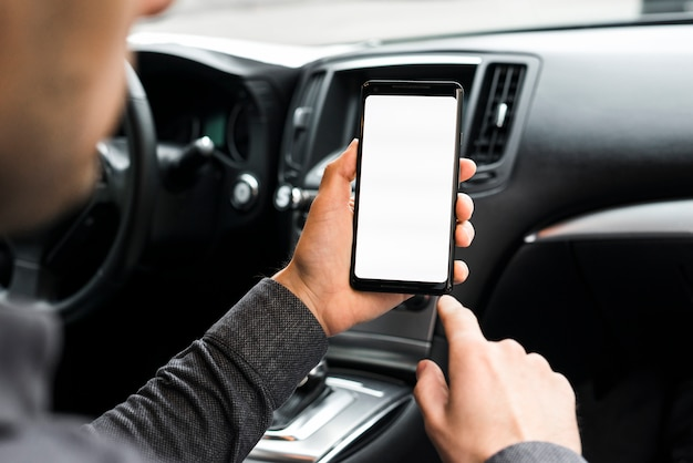 A businessman sitting in the car using mobile phone with white display screen