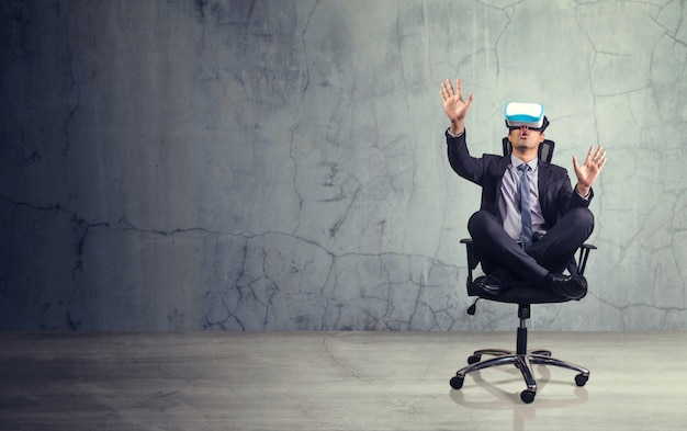Businessman sitting in chair wearing virtual reality glasses.