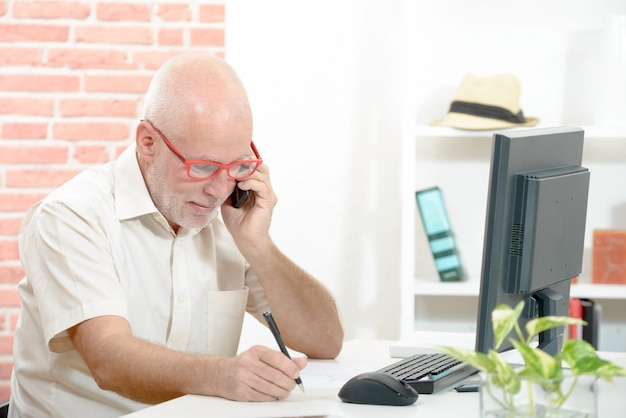 Businessman sitting at desk and talking on cellphone